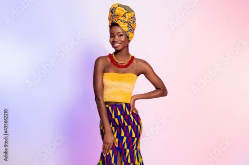 Fototapeta Photo of charming happy dark skin woman hold hand waist wear tribal outfit isola