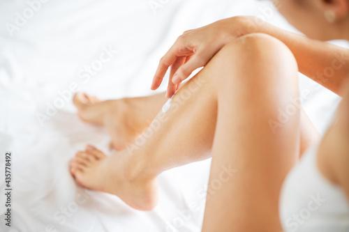 Foto Woman applying body lotion on her leg