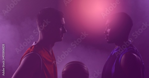 Composition of two basketball players holding ball on purple tinted background