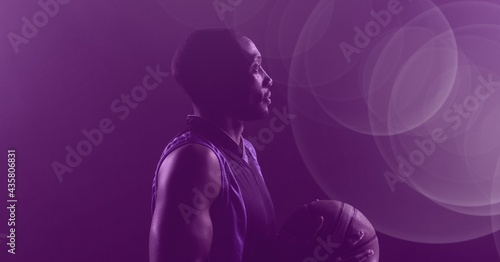 Composition of african american basketball player holding ball on purple tinted background