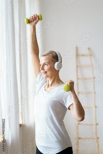 Smiling Senior Woman Exercising Fitness With Dumbbells Fotobehang