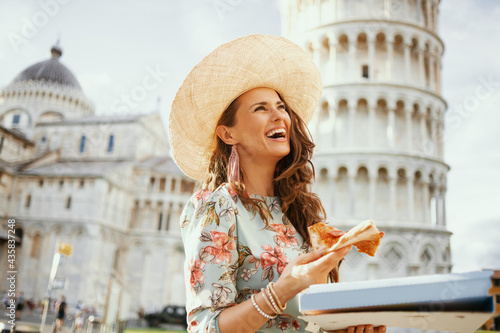 smiling trendy woman in floral dress with pizza and hat Fototapeta