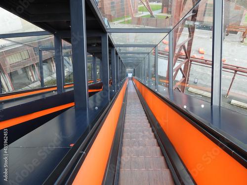 Canvas Print High angle shot of a descending escalator with orange stripes