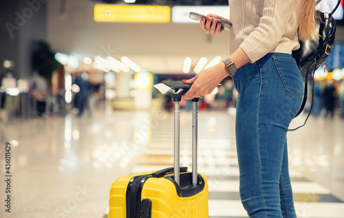 Stampa su Tela Young woman holding phone and yellow suitcase luggage with passport and plane ti