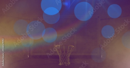 Composition of basketball basket with blue spots of light with prism on yellow tinted background