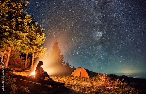 Young woman hiker sitting on bench near bonfire under magical sky with stars and Milky way Fotobehang