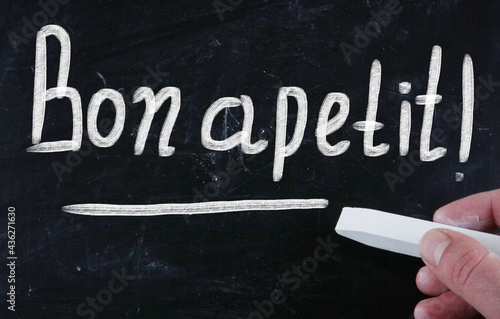 Obraz na plátně Closeup shot of a white text Bon apetit! on a black surface