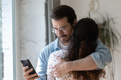 Foto Dishonest young man cuddling loving woman, using smartphone behind back, checking her calls or communicating with mistress