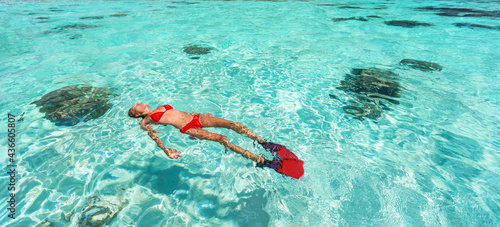 Fotografie, Obraz Snorkel woman swimming in the turquoise ocean sea relaxing floating on luxury travel vacation above underwater coral reefs