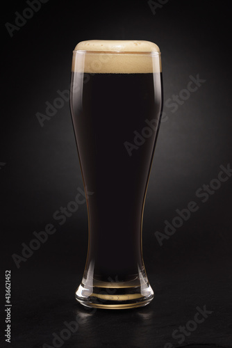 Wallpaper Mural Mug with fresh stout beer with cap of foam on a black.