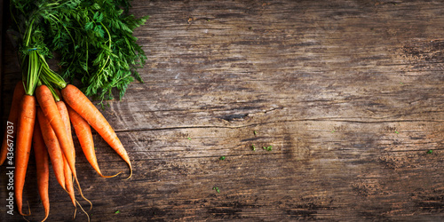 Cuadros en Lienzo Top view of fresh organic carrot roots on wooden textured kitchen table