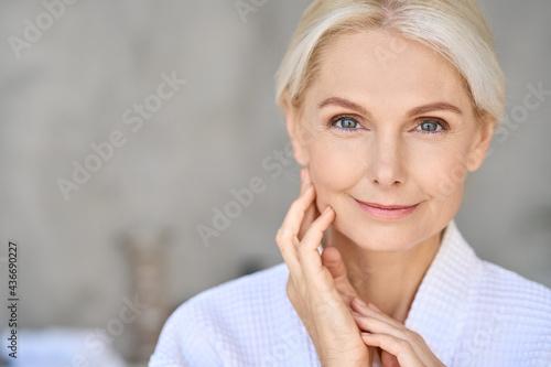 Fototapeta Closeup of happy smiling beautiful senior adult woman of 50s wearing bathrobe at spa hotel looking at camera touching face