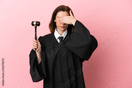 Fotografia Middle aged judge woman isolated on pink background covering eyes by hands