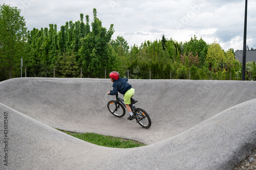 Young boy riding a pump track with bmx bike