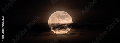 Fotografiet horizontal panoramic image of the full moon slightly obscured by clouds during t