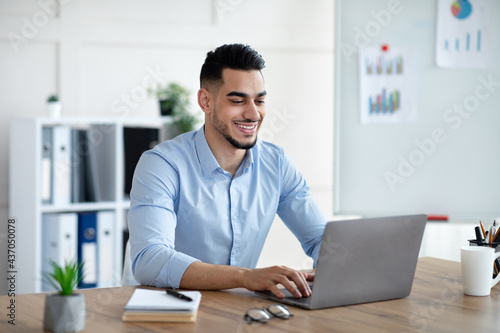 Handsome young Arab businessman working with laptop computer at his desk in offi Fototapet