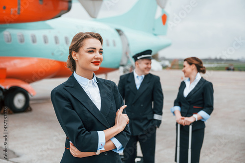 Photo Aircraft crew in work uniform is together outdoors near plane