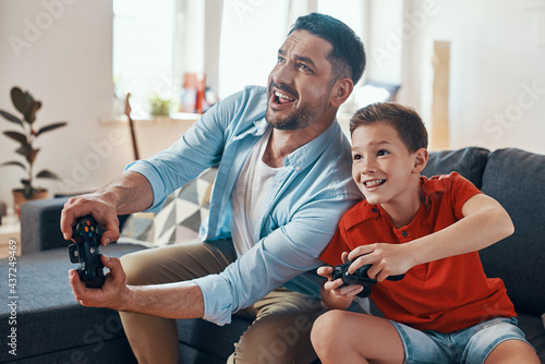 Fototapeta Happy young father and son playing video games while spending time at home