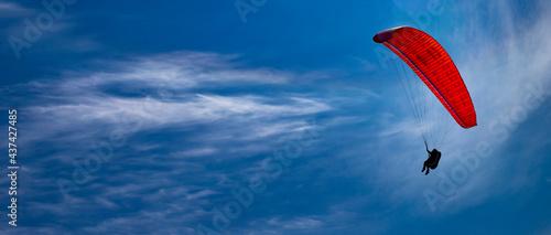 Obraz na plátně One paraglider flies on a red parachute in the blue sky