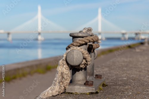 Fototapeta premium Old rope and mooring double cross bollard in sailing port. Cable-stayed bridge and blue water in the background. Summer sea travel concept