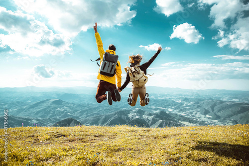Fototapeta Hikers with backpacks jumping with arms up on top of a mountain - Couple of youn