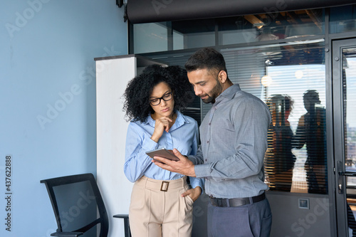 Fotografia Concentrated Indian male ceo businessman and female African American financial manager working on investment operations using tablet device standing in modern corporate office