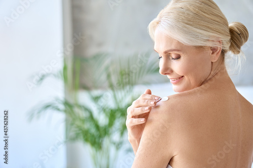 Canvas Back view of naked gorgeous middle aged 50s woman applying moisturizing body lotion after shower