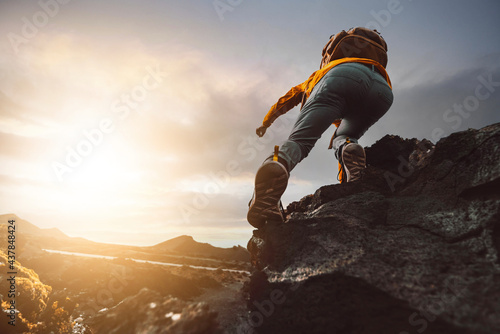 Foto Successful hiker hiking a mountain pointing to the sunset