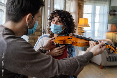 Photo Happy woman play violin under music teacher's instructions in mask during corona