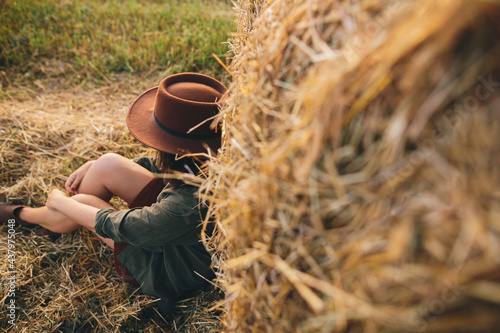 Beautiful stylish woman in hat sitting at haystacks in evening summer field Fototapet
