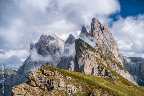 Fotografie, Obraz A man in front of epic Furchetta and Sass Rigais peaks in Seceda, Dolomites Alps, Odle mountain range, South Tyrol, Italy, Europe
