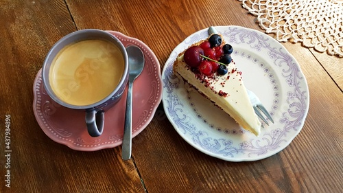 Fotografie, Obraz Black coffee and a slice of cake with fresh berries on a saucer are prepared for