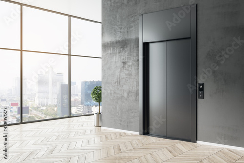 Stylish business center hall with black elevator, wooden parquet floor and city view from glass wall Fototapeta