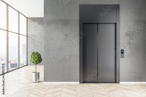 Fotografering Front view on stylish black elevator in business center area with light wooden floor, tree in metal flowerpot and big window with city view
