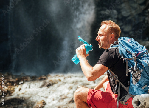 Fotografiet Man with backpack dressed in active trekking clothes drinking the water from touristic flask sitting near mountain river waterfall and enjoying the Nature