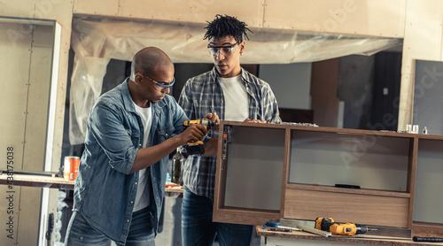 Fotografija Two young black man carpenter assembling furniture part in they workshop
