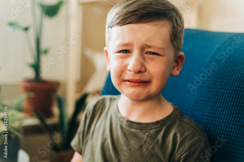 Canvas Close up portrait of crying little kid boy, sitting on couch indoors at home