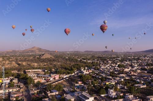 Globos aerostáticos volando cerca del templo del sol de Teotihuacan en México, amanecer con la luna, azul colorido