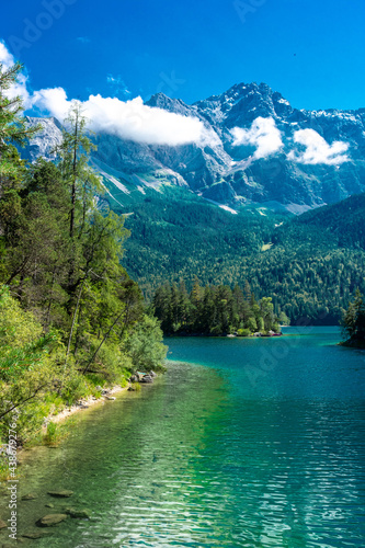 Fotografiet Faboulus landscape of Eibsee Lake with turquoise water in front of Zugspitze summit under sunlight