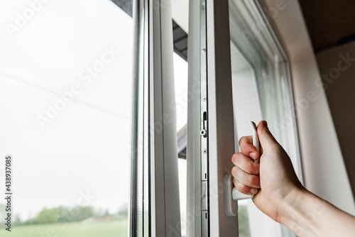 Hand opens white plastic window.