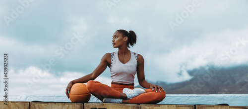 Tableau sur Toile Athlete woman relaxing with basketball outdoors