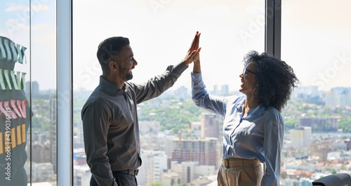 Happy cheerful successful business partners indian businessman and African American businesswoman giving high five celebrating project victory standing in office near urban view panoramic window.