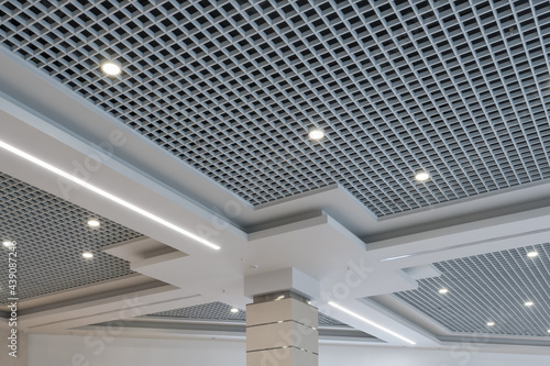 Foto suspended and grid ceiling with halogen spots lamps and drywall construction in empty room in store or house