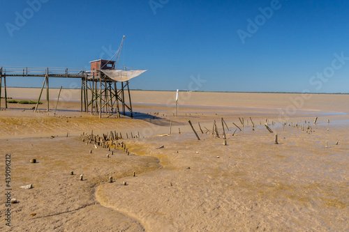 Canvas Print Traditional fishing hut on stilts situated on tidal estuary mudflats at low tide