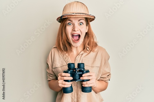 Fotografia Young caucasian woman wearing explorer hat looking through binoculars celebrating crazy and amazed for success with open eyes screaming excited