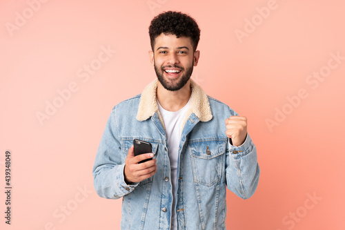 Tela Young Moroccan man using mobile phone isolated on pink background celebrating a