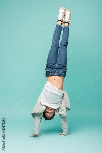 Fotografiet happy boy in denim jeans doing handstand on blue.
