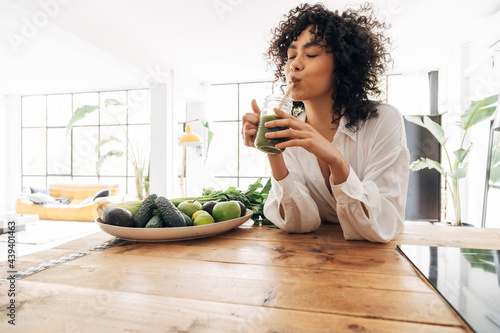 Young african american woman drinking green juice with reusable bamboo straw in Fototapet