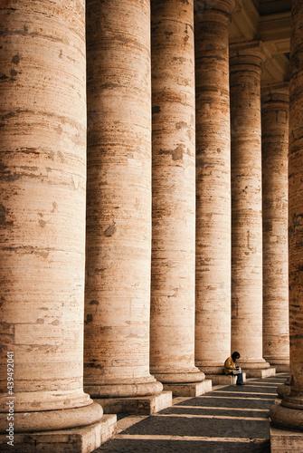 Fotografía A woman sit below Colonnades of St Peter's Square, reading a book, Vatican