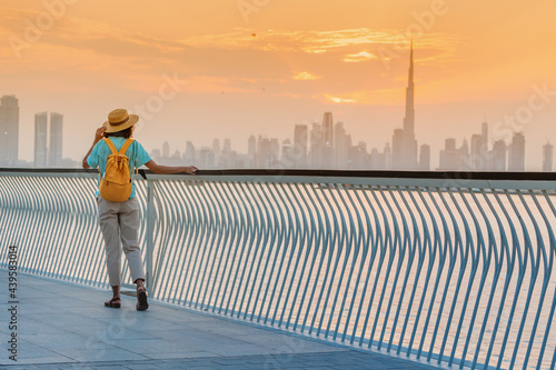 Fotografía A happy traveler woman with a hat and a yellow backpack enjoys a stunning panora